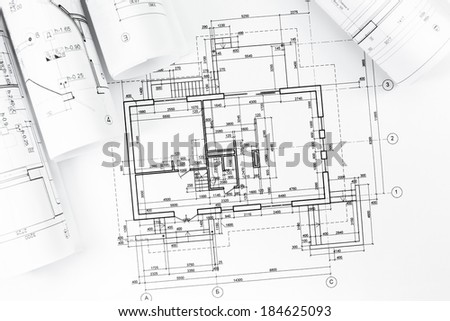Architectural background with floor plans and rolled technical drawings  - stock photo