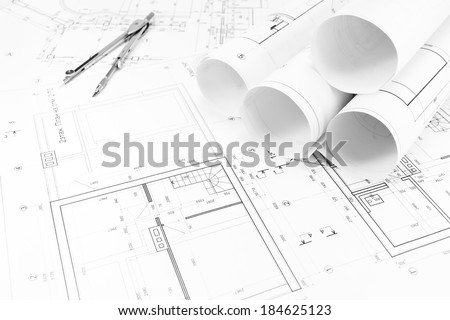 Architectural background with floor plans and rolls of technical drawings - stock photo