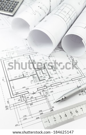Architectural background with floor plans, rolls of technical drawings and work tools - stock photo