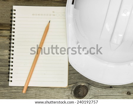 Architectural blueprint of office building with a pencil,notebook on wood table - stock photo