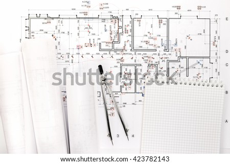 architectural blueprints and blueprint rolls with drawing compass and notepad - stock photo