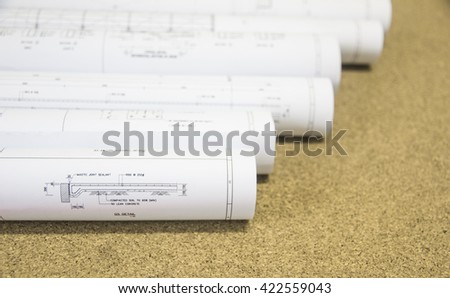 Architectural blueprints and rolled House Blueprints and Construction Plans of architectural project on white background over blurred blueprint. - stock photo