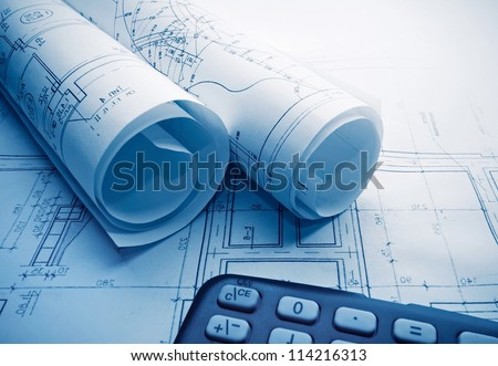 Architectural blueprints rolls and calculator - stock photo