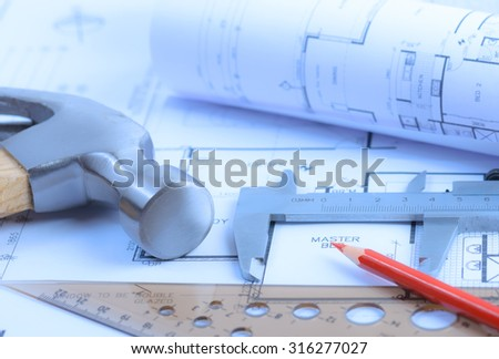 Architectural blueprints rolls and engineering items. Toned in blue. Soft light - stock photo