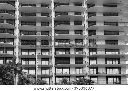 Architectural building for vacation rental in Miami Style Florida   Modern art deco residential building in black and white with palm trees, image for architecture travel real estate business blog - stock photo