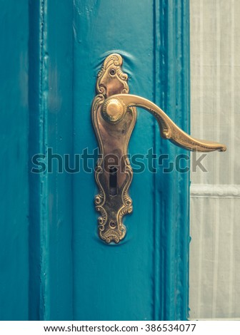 Architectural Detail Of A Vintage Brass Door Handle On A Blue Painted Door - stock photo