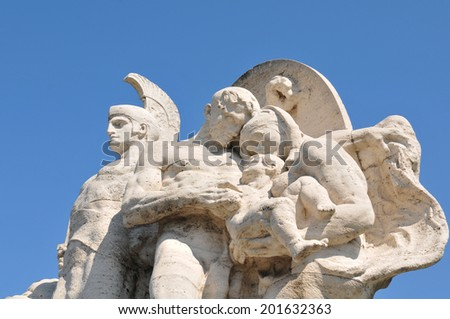 Architectural detail of ancient statue representing Roman soldier and family against blue sky - stock photo