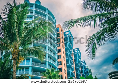 Architectural flat building Miami Style South Beach Florida image retro filtered  Modern art deco condominium construction aqua and apricot color with palm trees against blue tropical sky background - stock photo