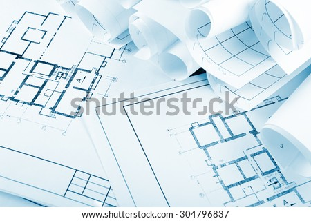 Architectural project, blueprints, blueprint rolls on plans. Engineering tools view from the top. Copy space. Construction background. Blue toned - stock photo