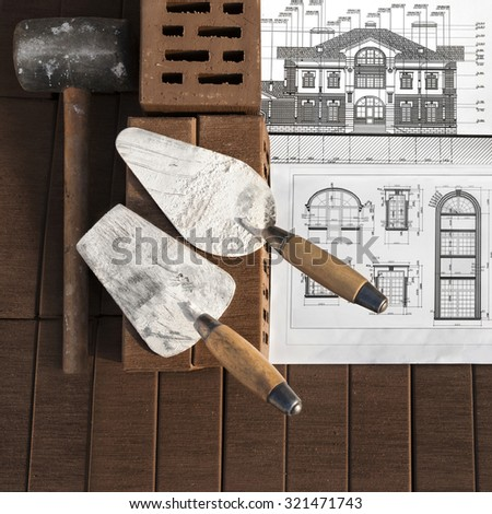 Architectural project with brick and tools on brown brick background. Focus on foreground. - stock photo
