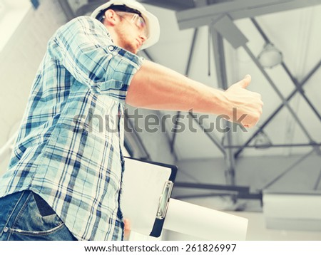 architecture and home renovation concept - man in helmet and gloves with blueprint showing direction - stock photo