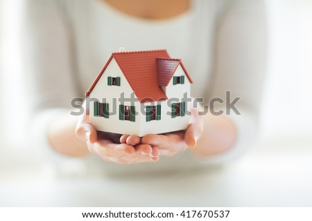 architecture, building, construction, real estate and property concept - close up of hands holding house or home model - stock photo