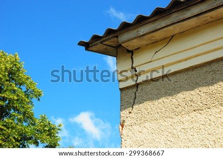 Architecture detail of damaged house corner dilapidated old building facade wall over blue sky background. Private abandoned home fall to ruin - stock photo