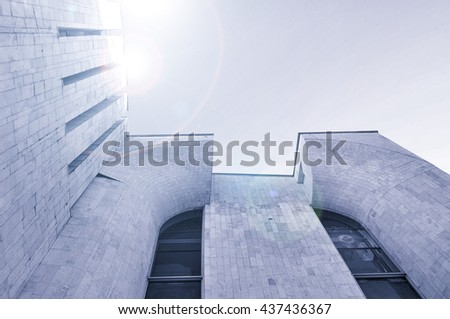 Architecture modern background - perspective bottom view of high building architecture details of concrete and glass . Black and white tones applied. Architecture futuristic cityscape in cold tones. - stock photo
