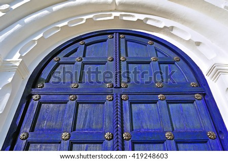 Architecture texture background. Aged wooden dark blue door with metallic rivets and upper arch of white stone - colored architecture background - stock photo