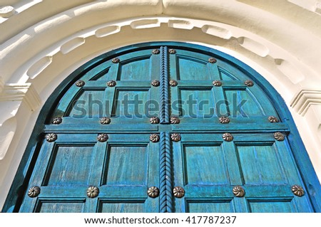 Architecture texture background. Aged wooden turquoise door with steel rivets and upper arch of white stone - colorful architecture background - stock photo