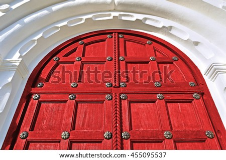 Architecture view. Architecture detailed background - aged wooden door of red color with metal rivets and upper arch of white stone - vintage architecture background - stock photo