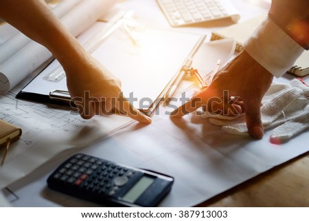 Architectures working or discussing on his plane project at site - stock photo