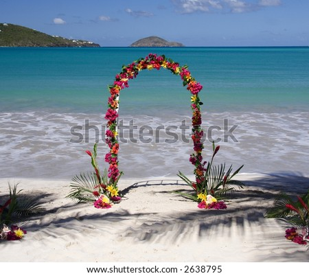 Archway decorated with colorful flowers on a caribbean beach - stock photo