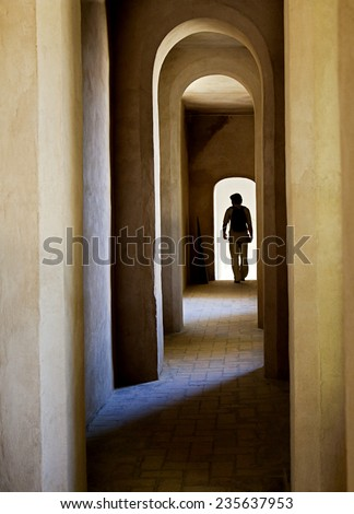 Archway in a medieval castle in Spain and a silhouette of a tourist - stock photo
