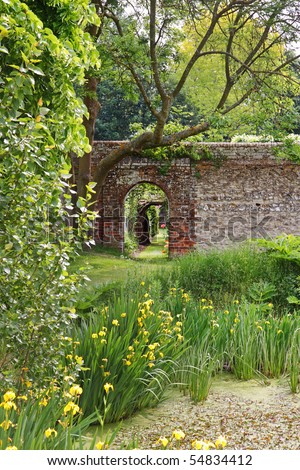 Archway into an English Walled garden with irises around a pond - stock photo