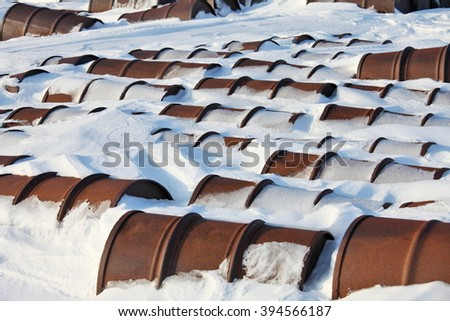 Arctic coast pollution. Rusting discarded oil barrels, oil drums in the arctic snow near abandoned polar settlements and stations - stock photo