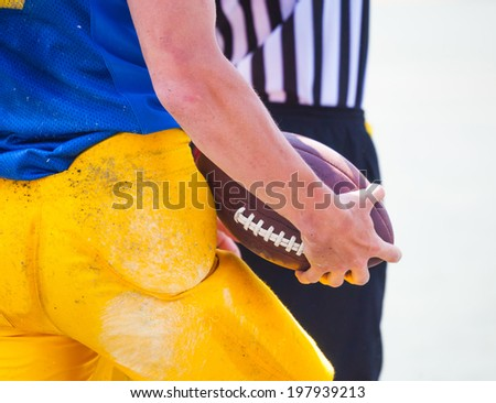 are referees and american football player holding the ball in his hands - stock photo