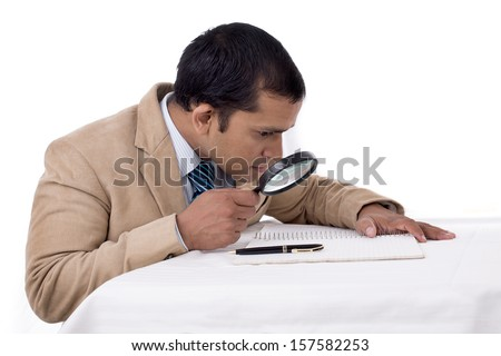 Are you Curious enough ? Indian Detective agent searching for something with a magnifying glass. Isolated on white. - stock photo