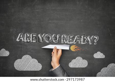 Are you ready concept on black blackboard with businessman hand holding paper plane - stock photo
