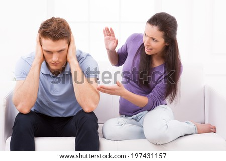 Are you with me? Furious young woman shouting and gesturing while man sitting close to her on the couch and holding head in hands  - stock photo