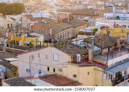 Areal view, as seen from the city gate, on the old city of Valencia, Spain, with beautiful rimlights of the late afternoon sun at sundown - stock photo