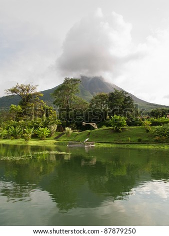 Arenal volcano in Costa Rica on a clear day. Smoke & steam coming out from the top cone - stock photo