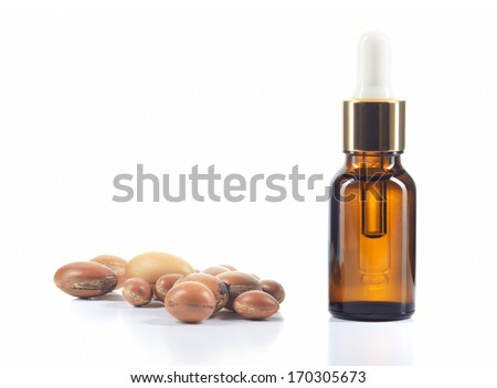 Argan oil and group of argan nuts isolated on white background. Body oil in brown bottle. - stock photo
