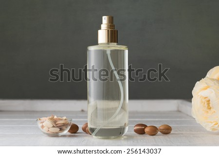 Argan oil in a glass bottle with argan fruit - stock photo