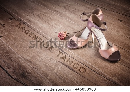 """Argentine tango shoes and a dry rose on a wooden floor, caption """"Argentine tango"""" - stock photo"""
