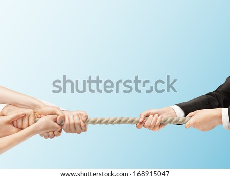 arious hands during tug war on blue backgrounds - stock photo