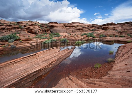Arizona Desert Pond, Small Lake in the rock formations with sky reflection - stock photo