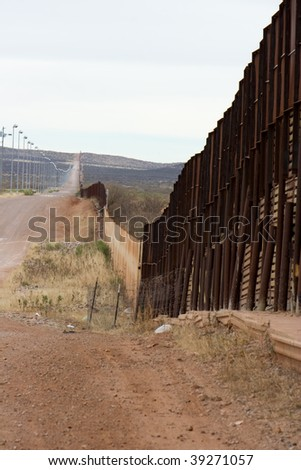 Arizona-Mexico border wall and road - stock photo