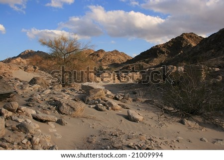 Arizona, USA; desert scene, rocks, sand in foreground, mountains in background; late afternoon, wintertime; blue sky, some cloud - stock photo