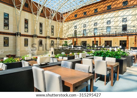 ARLAMOW HOTEL, POLAND - AUG 3, 2014: tables in beautiful open lobby restaurant in Arlamow Hotel. This luxury resort was owned by Poland's government and is located in Bieszczady Mountains. - stock photo