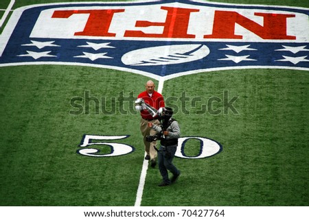 ARLINGTON - JAN 26: In preparation for the Packers Steelers Super Bowl XLV an unidentified cameraman and worker carry the trophy off the Cowboys Stadium field. Taken January 26, 2011 in Arlington, TX. - stock photo