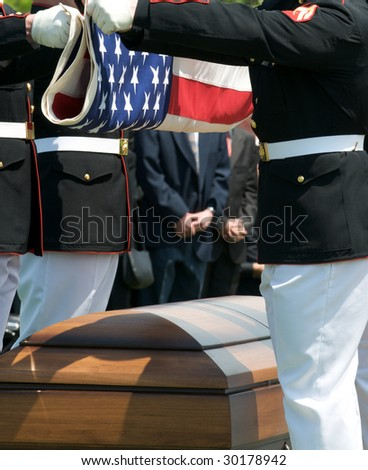 Arlington National Cemetery with military Honor Guard folding flag above casket - stock photo