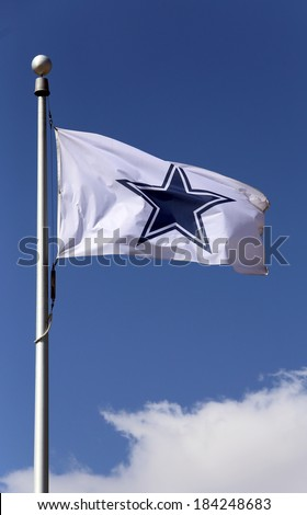 ARLINGTON, TX - MARCH 14: A Dallas Cowboys flag flies in front of the AT&T Stadium located in Arlington, Texas on March 14, 2014. AT&T Stadium is home to the Dallas Cowboys of the NFL. - stock photo