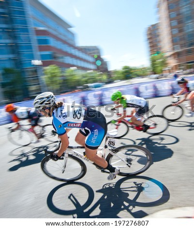 ARLINGTON, VIRGINIA - JUNE 7: A cyclist competes in the Clarendon Cup elite women's race at the Air Force Cycling Classic on June 7, 2014 in Arlington, Virginia - stock photo