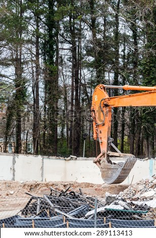 Arm and bucket on an orange front end loader at a demoliton site - stock photo