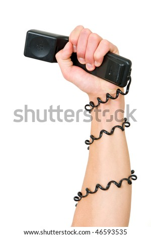 Arm and clenched fist, holding a telephone, with the wire wrapped around the arm, illustrating the power of a telephone service, call center or phone terror - stock photo