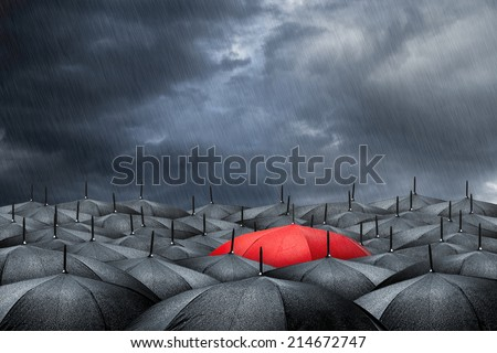arm with red umbrella in mass of black umbrellas  - stock photo