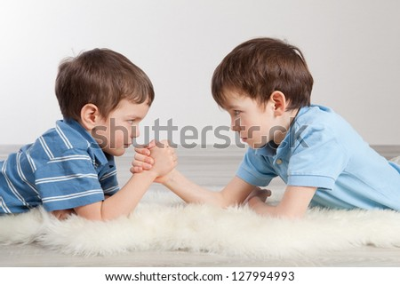 Arm wrestling and two brothers, indoor - stock photo