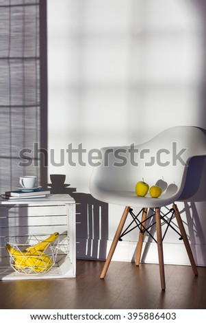 Armchair and coffee table made of box in spacious bright living room with wooden floor - stock photo