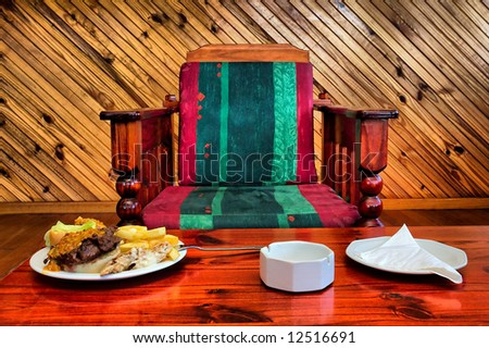 Armchair and table with food in restaurant. Shot in Sodwana Bay campsite, KwaZulu-Natal province, Southern Mozambique area, South Africa. - stock photo